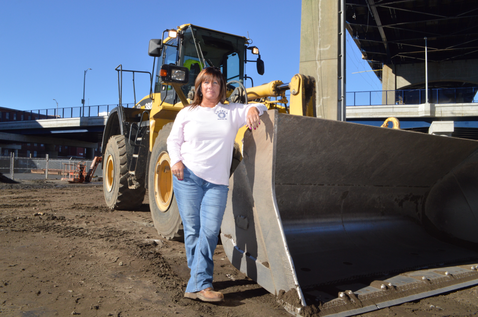 Heavy operating engineer Debbie Currie with the front-end loader she operates at work on the Route 79/Braga Bridge Improvements Project in Fall River, Massachusetts, Nov. 18, 2016.