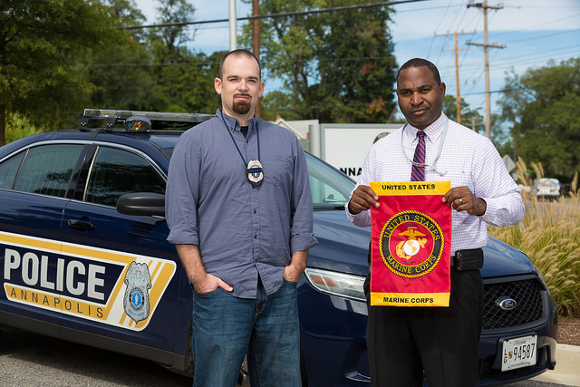 Two veterans who now work as police officers stand next to a squad car.