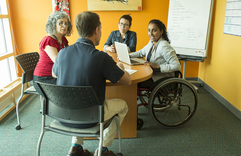 A group of colleagues sit together around a desk, including a woman who uses a wheelchair.