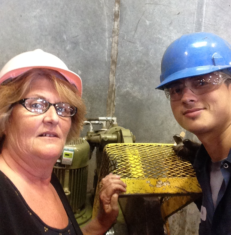 Lisa and employee Delfino Uteras discuss safety procedures for the copper cutter.