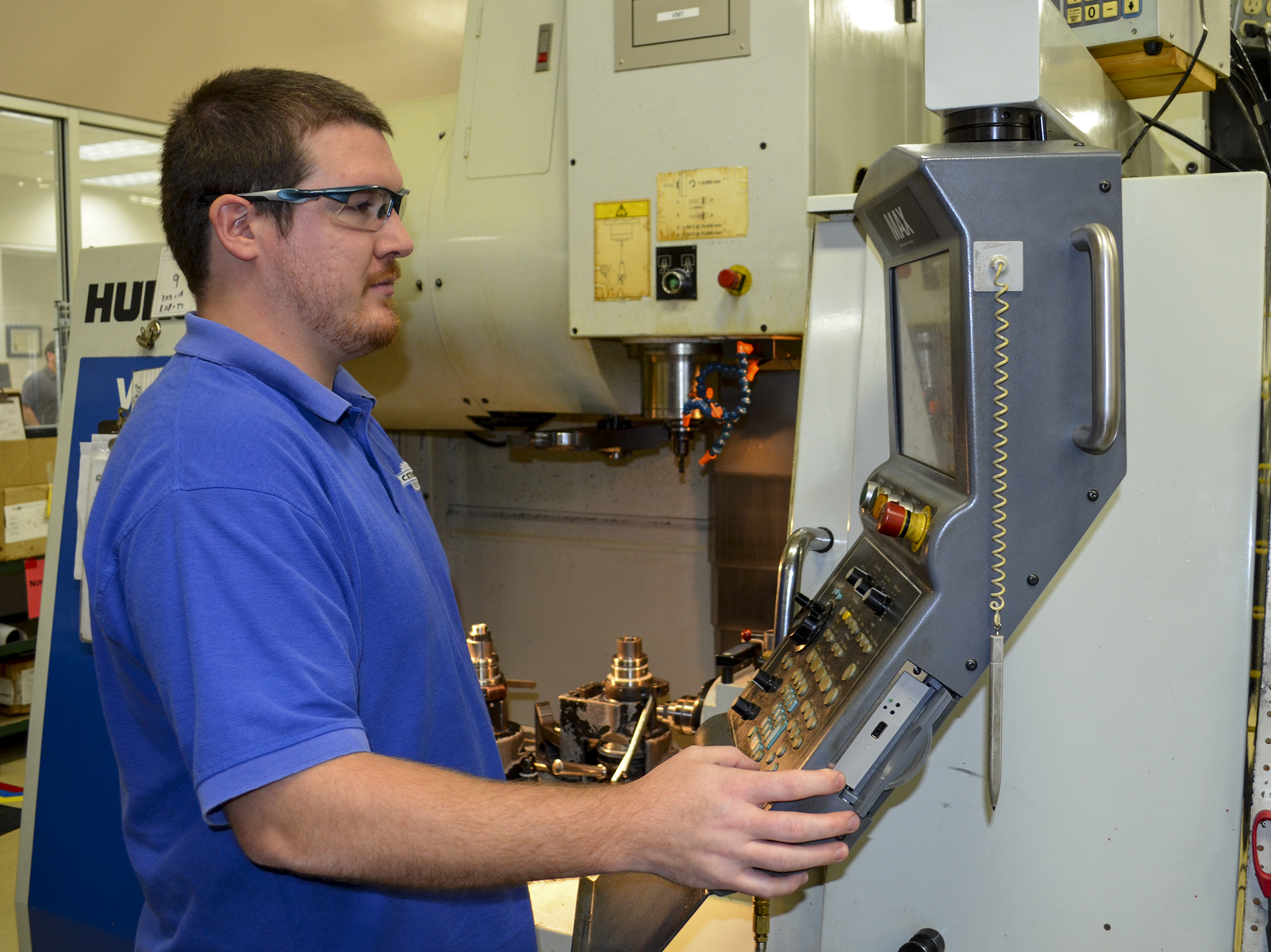 Andrew Rungren operates a CNC mill to manufacture a part.