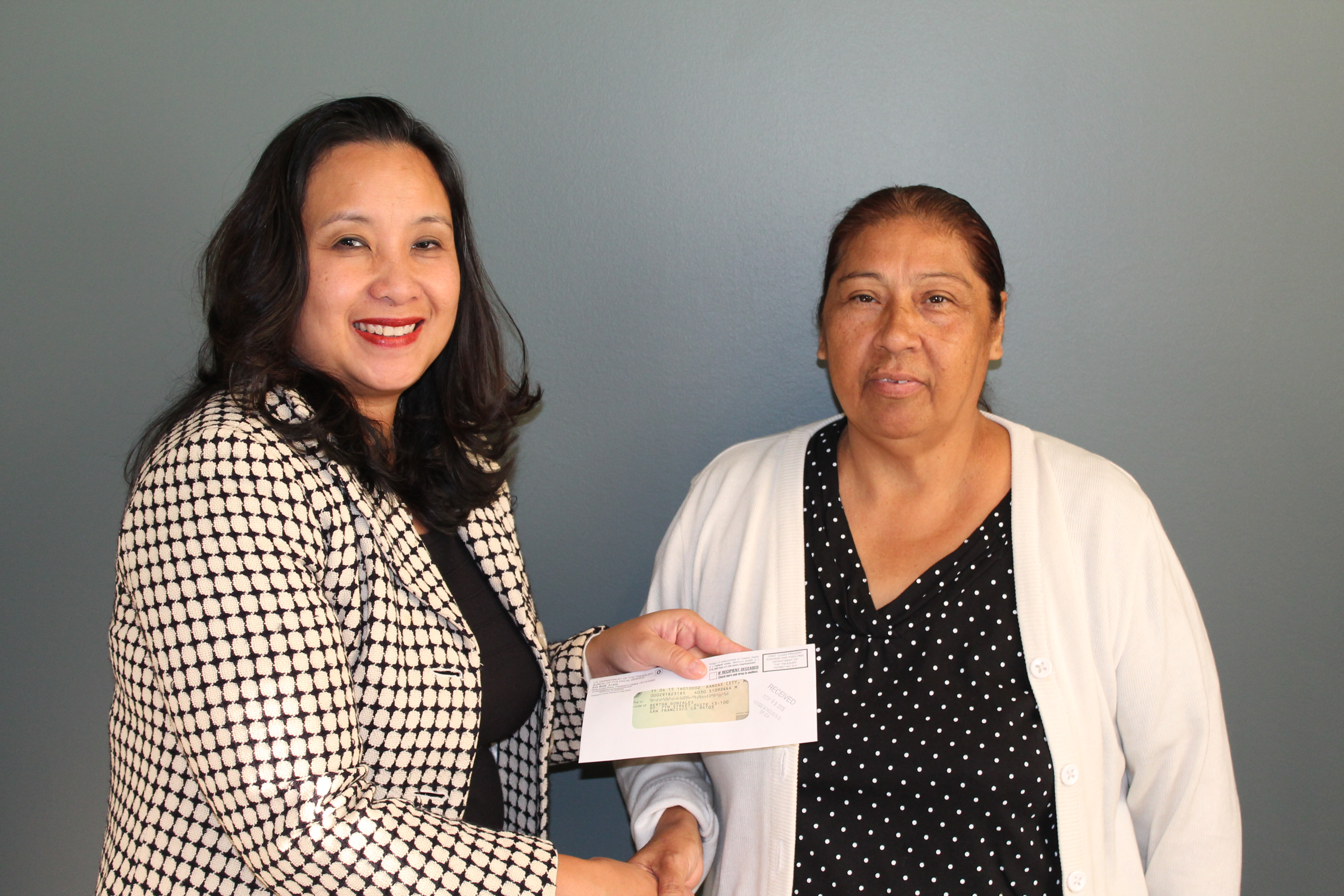 Bertha Gonzalez (right) receives a check for back wages from Kimchi Bui, district director for the Wage and Hour Division in Los Angeles.
