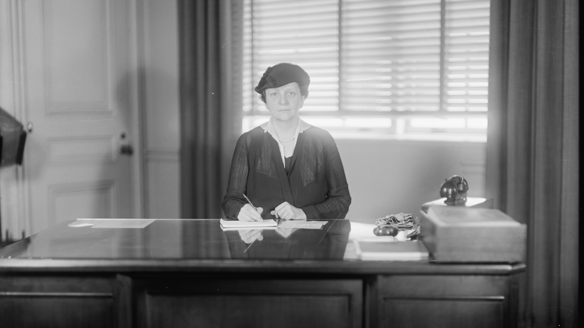 Frances Perkins at her desk wearing a tricorn hat