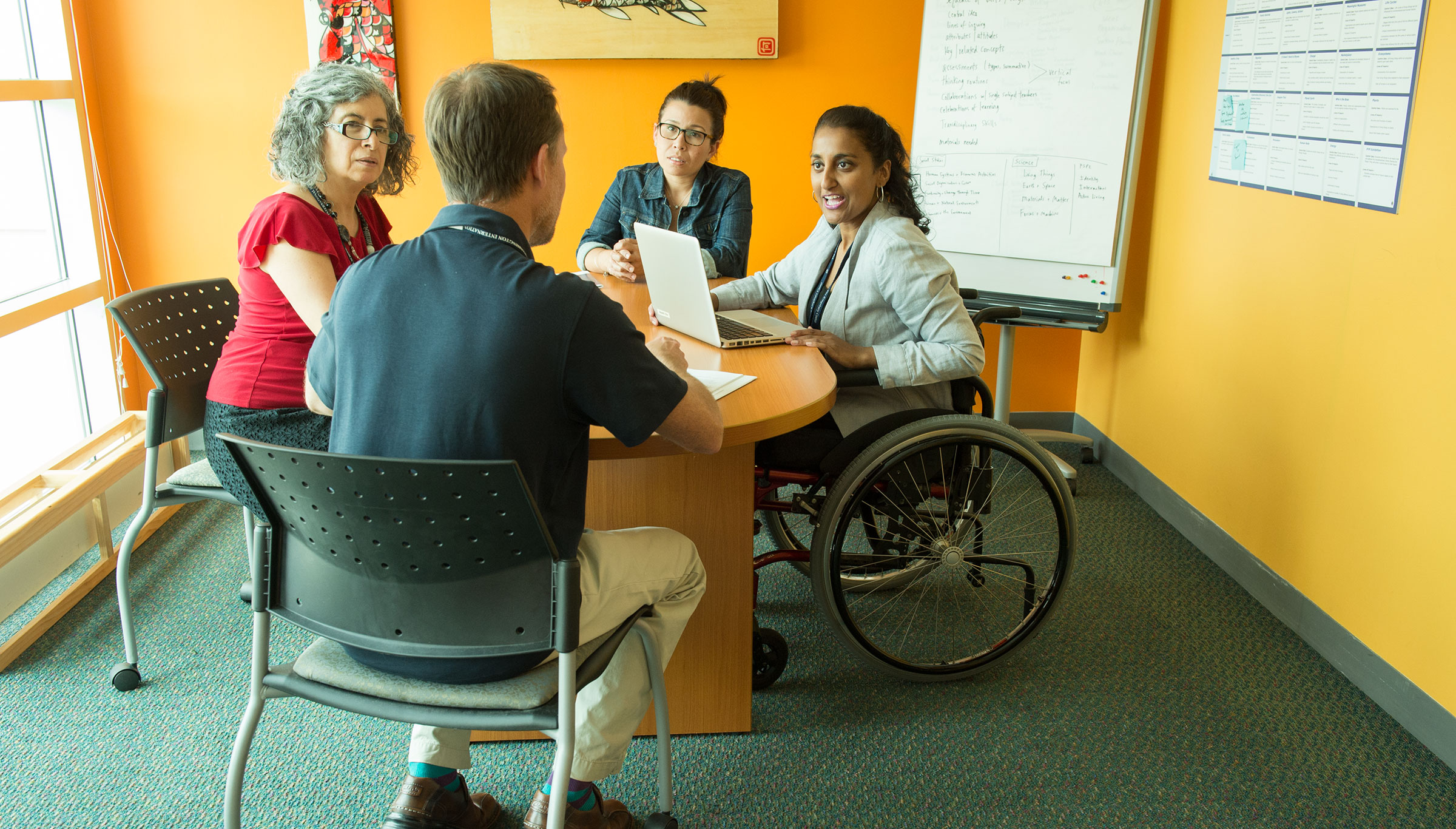 A photo of an inclusive workplace, with four men and women seated around a table in a conference room. One of the women is using a wheelchair.