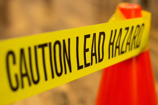 "Yellow tape that says: ""Caution lead hazards"""
