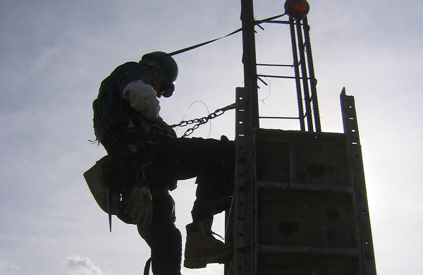 a worker climbs a piece of scaffolding wearing proper fall protection