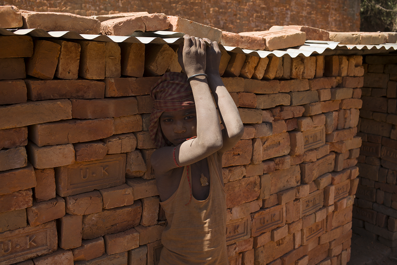 A boy child laborer stands in front of a brick wall in a desert country