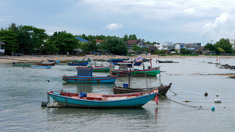 Photo of a Thai fishing village with several boats in the water