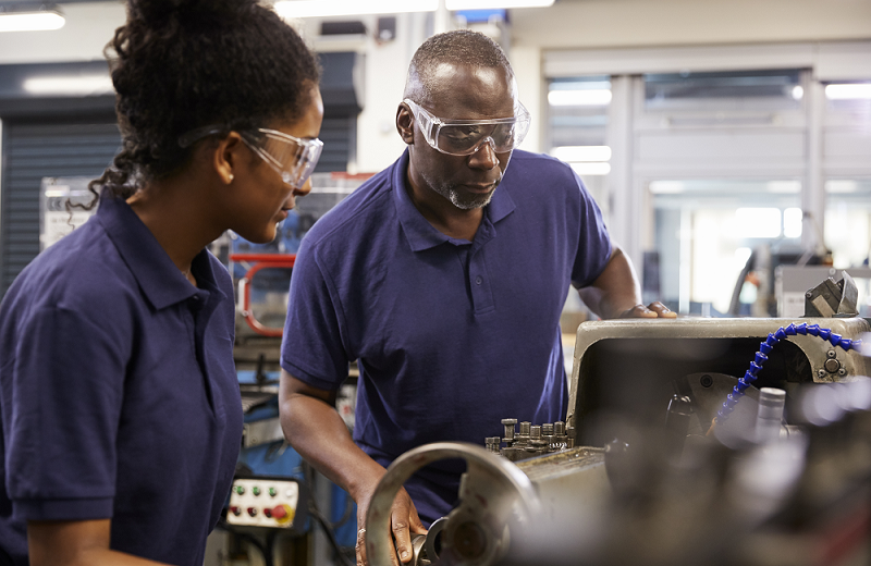 A young woman apprentice learns how to work in a machine shop from a mentor