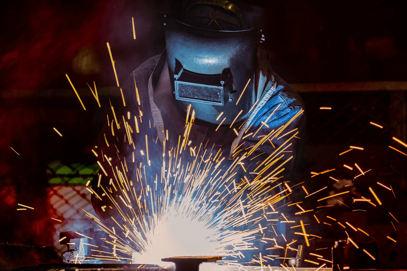 A welder with a protective face mask works, causing sparks to fly
