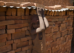 A boy child laborer stands in front of a brick wall