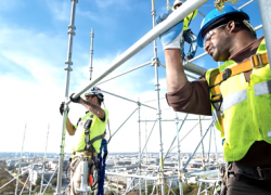 Two men working at heights wear fall protection gear