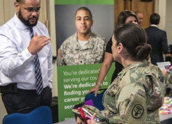Photo from job fair of a civilian employer speaking with a service member