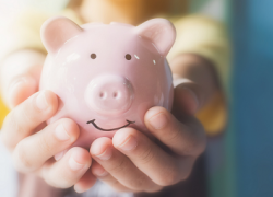 Woman holding a smiling piggy bank