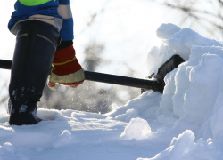 A worker shovels snow