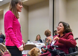 ODEP Senior Policy Advisor Nadia Mossburg (right) with her service dog Watson talk with Illinois State Sen. Laura Fine at the Women in Government Annual Conference in October 2018.