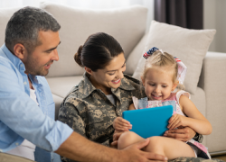 A service member reads to her young daughter while her husband looks on