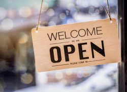 "A sign hangs in a shop window that says ""welcome, we are open, please come in"""