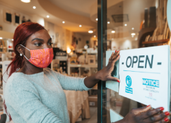 "A woman wearing a mask hangs an ""open"" sign on the door of her business."